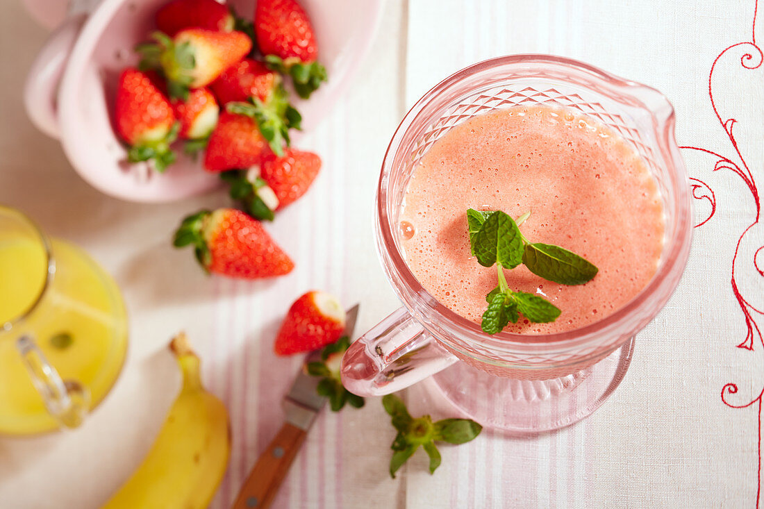 Strawberry smoothie with banana, orange juice, mint and honey in a glass jug