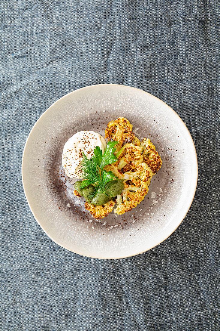 Roasted cauliflower with dill pesto and ricotta sumach cream (Levant cuisine)