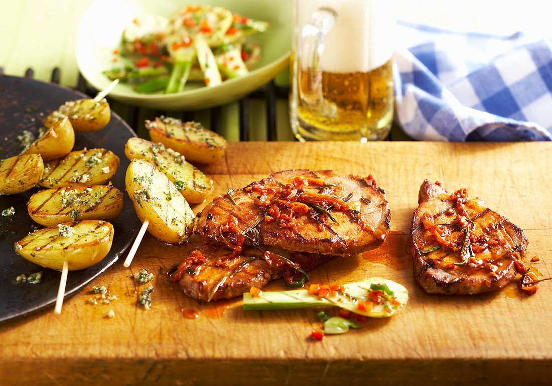 Grilled, marinated pork collar steaks with potato skewers and fennel salad (USA)