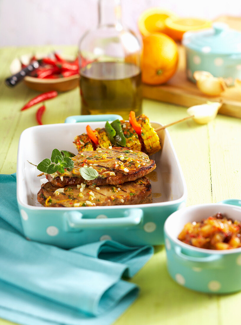 Pork collar steaks in a spicy orange marinade with grilled corn cob skewers and apple chutney