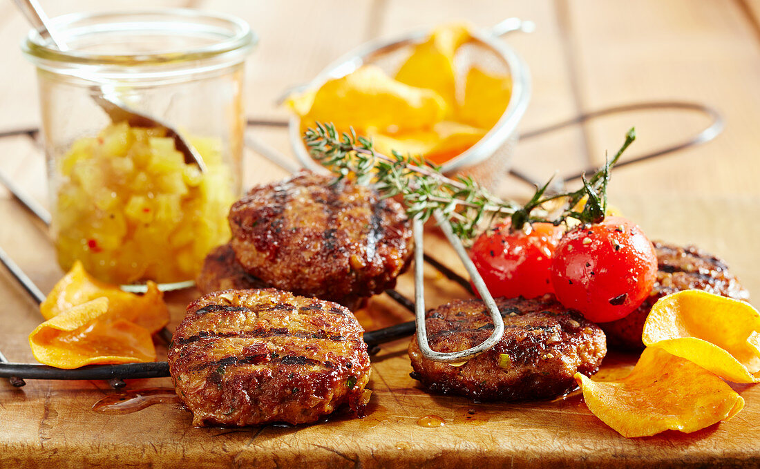 Grilled meat patties with pineapple chutney, cherry tomatoes and sweet potato crisps (Caribbean)
