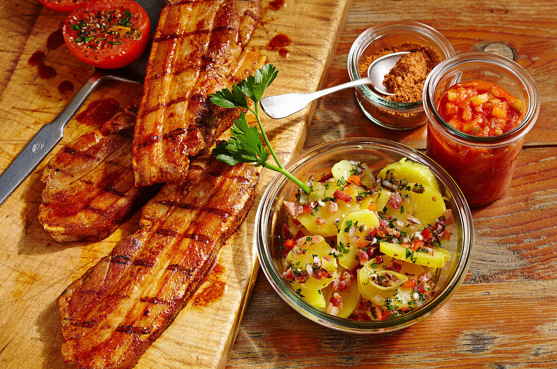 Grilled pork belly slices with potato salad in a preserving jar, a spice mixture and BBQ sauce