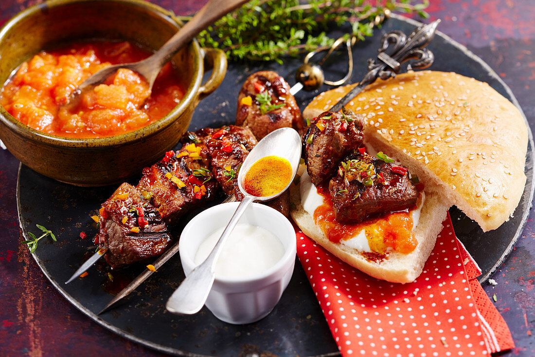 Yogurtlu kebab (grilled Turkish lamb skewers) with unleavened sesame seed bread, tomato sauce and yoghurt sauce