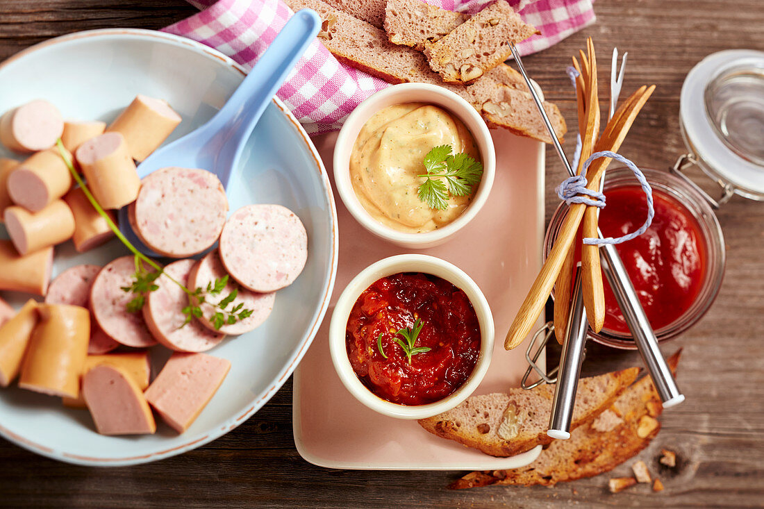 Ingredients for a sausage fondue with various sauces