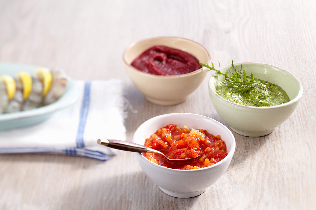 Bowls of various sauces for a fish fondue (exotic chutney, beetroot and horseradish dip, rocket and nut pesto)