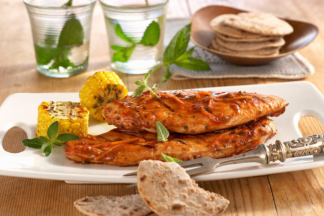 Grilled turkey steaks in a chilli and orange marinade with corn on the cob and mint parathas
