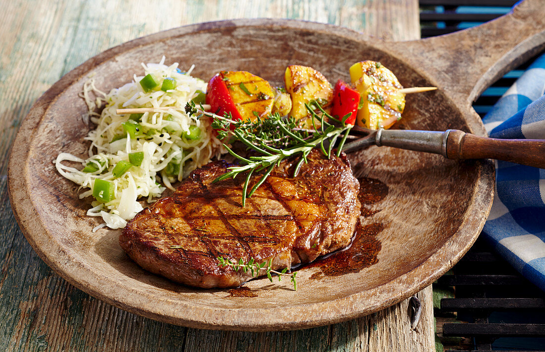 Marinated, grilled rib-eye steak with coleslaw and potato skewers on a wooden plate