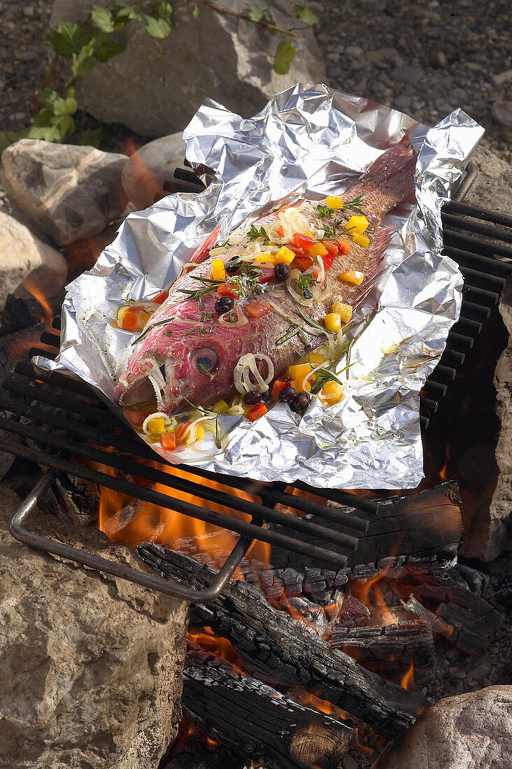 A whole red snapper in aluminium foil on a barbecue