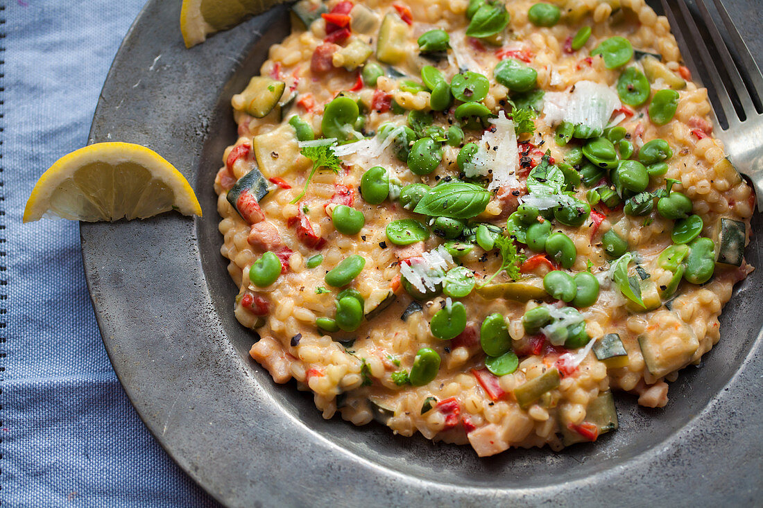 Barley risotto with bacon, basil, broad beans, peppers and zucchini