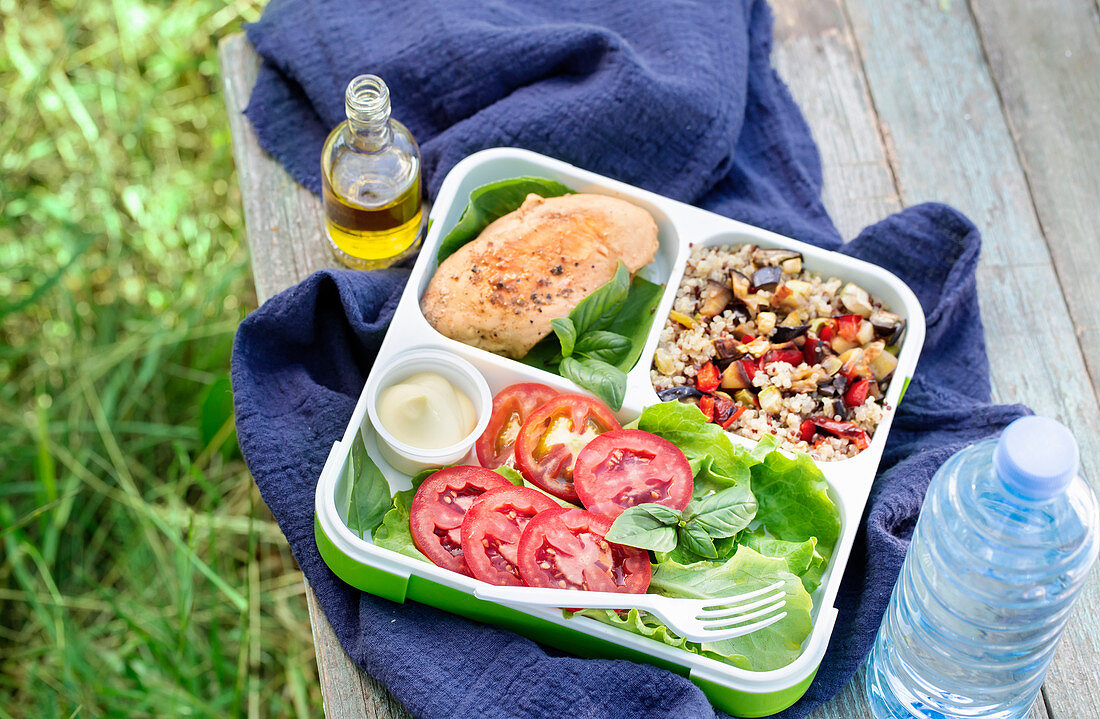 Lunch box with stewed chicken quinoa with vegetables and salad. Outdoors shot