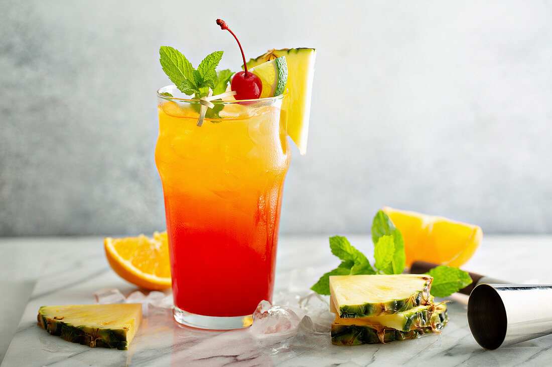 Tequila sunrise cocktail with pineapple and orange