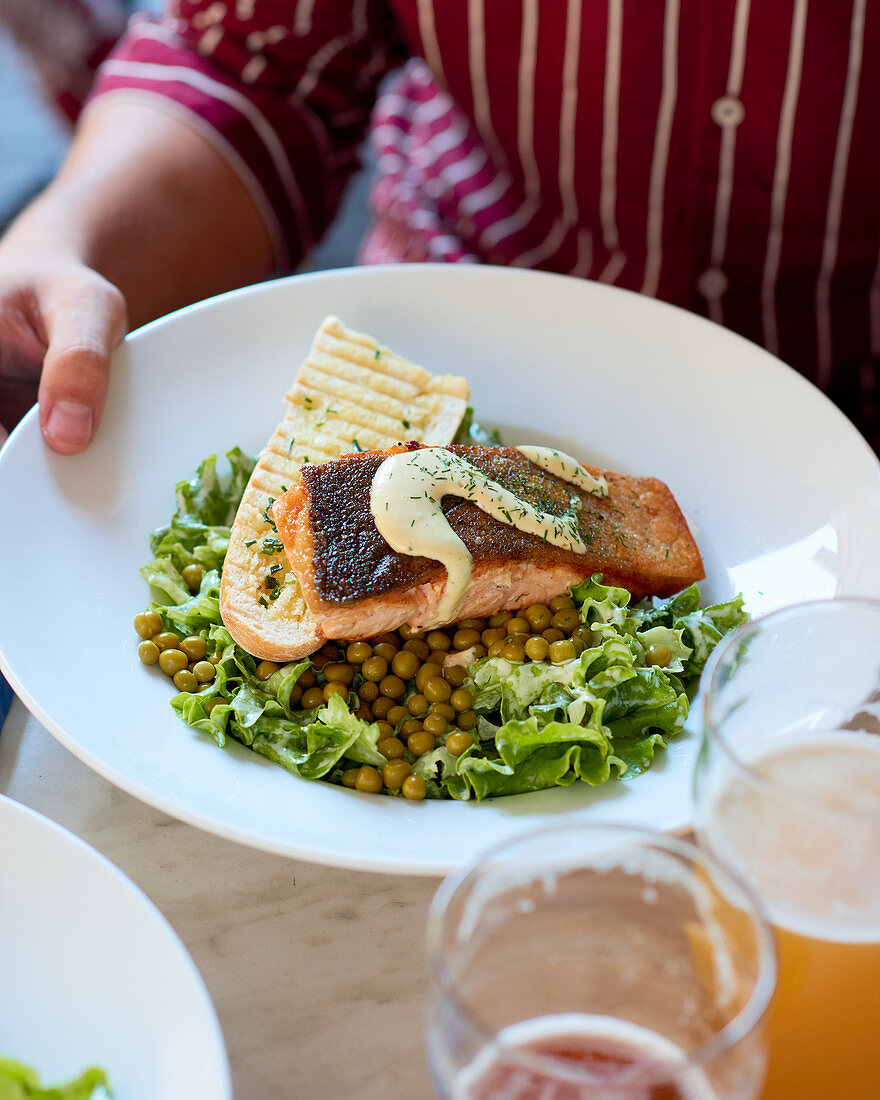 Green salad with peas, roasted salmon and grilled baguette.
