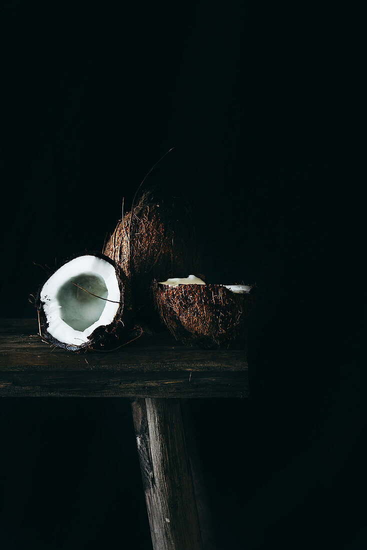 Coconuts on a wooden surface, one whole and one opened