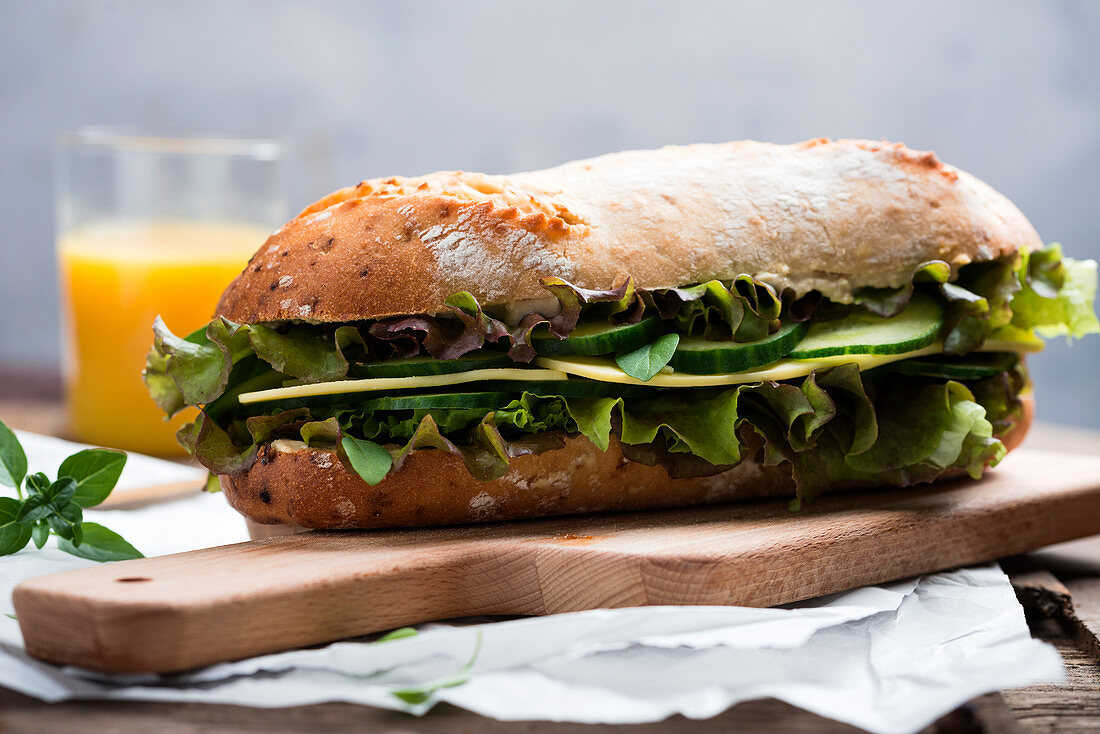 Onion baguette topped with substitute cheese, lettuce and cucumber