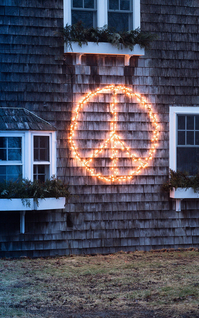 Peace symbol made from fairy lights on shingle facade of house