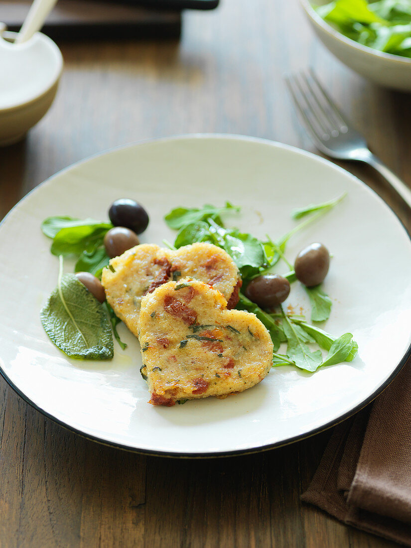 Heart-shaped semolina fritters on herb salad with olives