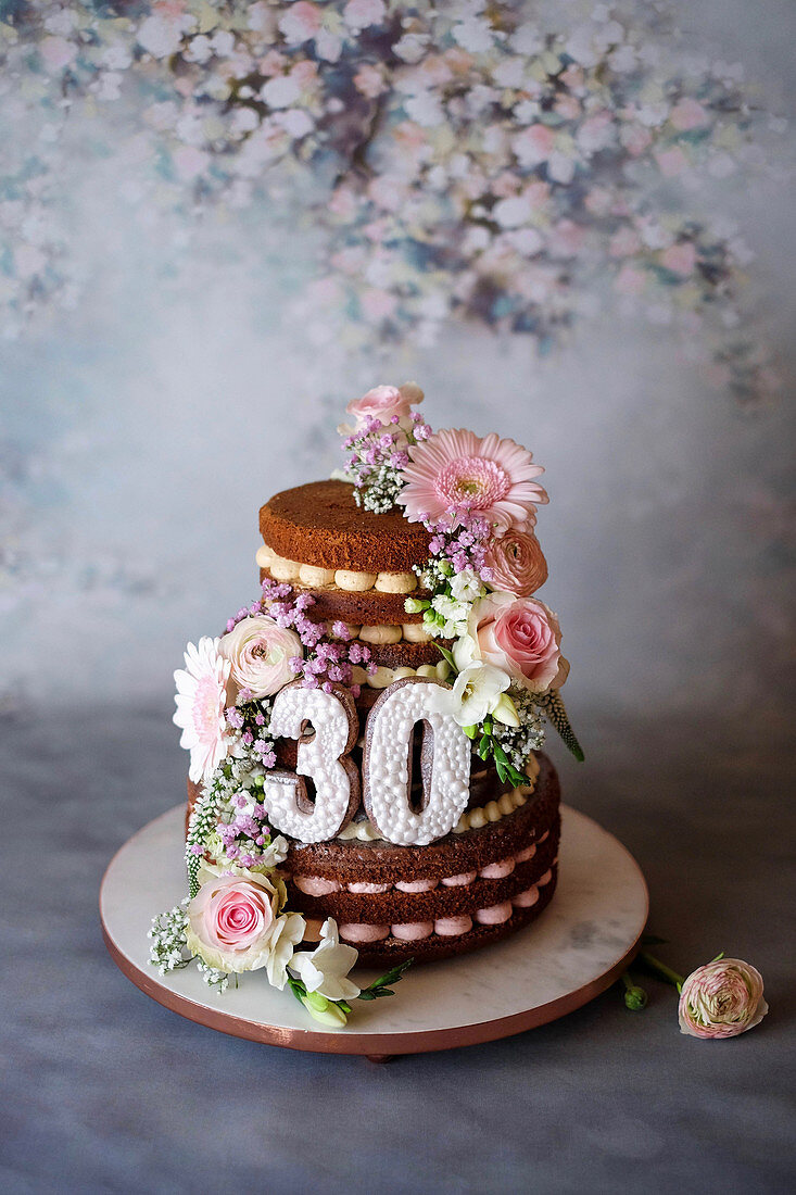 A naked cake decorated with fresh flowers for a pearl wedding anniversary