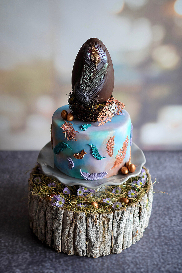 A mini Easter cake topped with a peacock feather chocolate egg