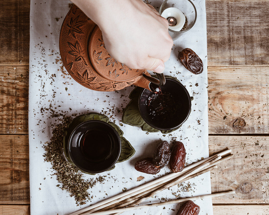 Hand serving fragrant tasty tea in cup clay teapot and sweet dates on white tray decorated with tea leaves