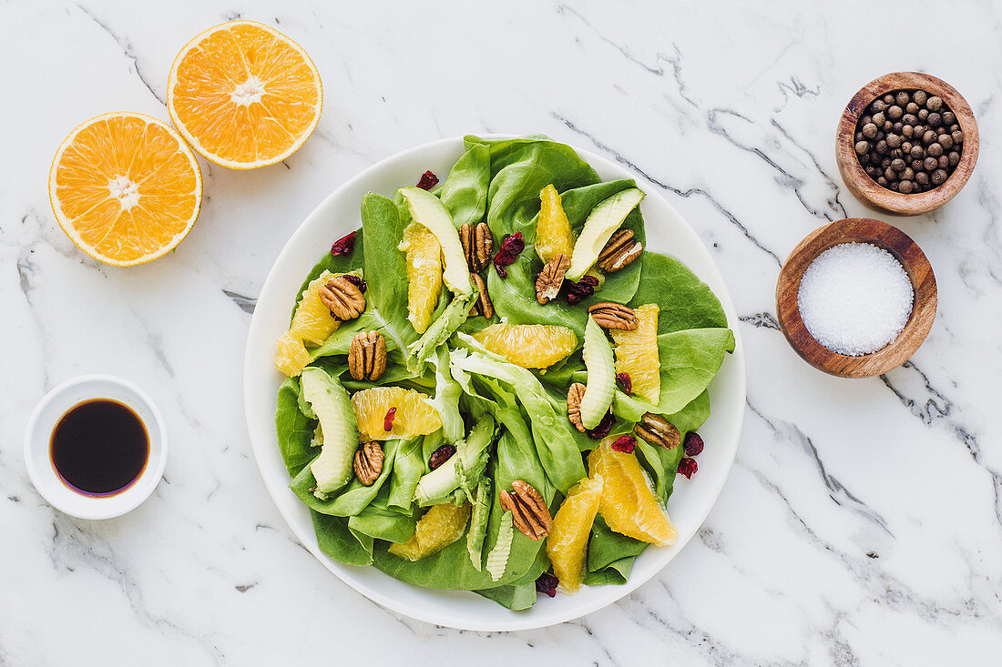 Served bowls with cut avocado, orange with pecan and cranberries
