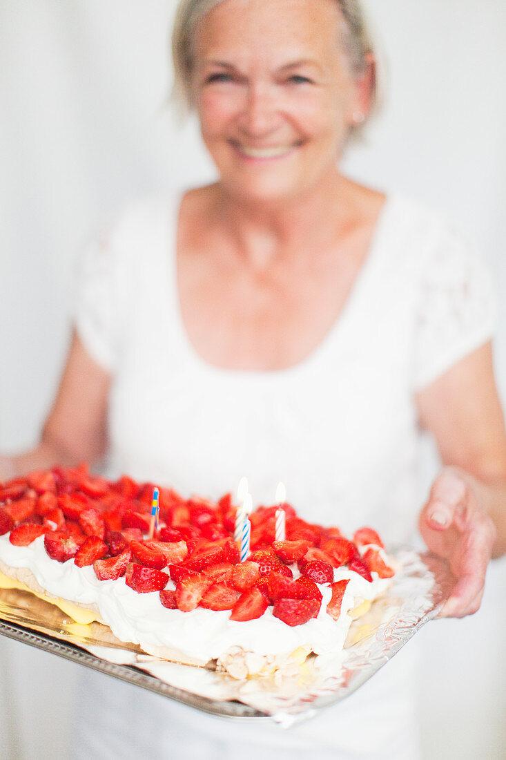 Senior woman holding strawberry cake, studio shot