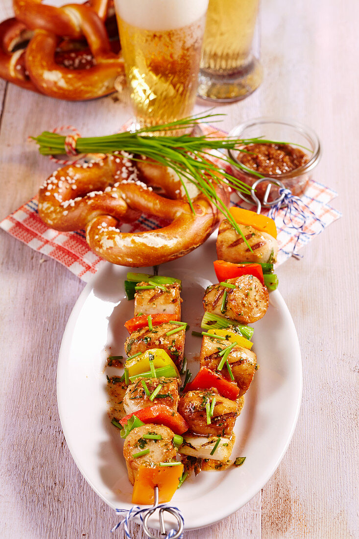 Bavarian white sausage and vegetables skewers with a white beer marinade, mustard, vegetables, pretzel and chives