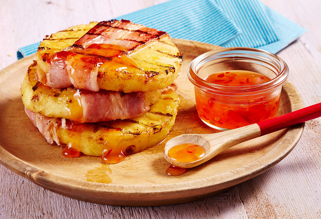 Grilled bacon and pineapple slices with a sweet and spicy chilli sauce on a wooden plate