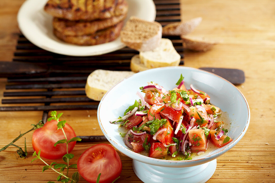 Grilled pork collar steaks in an orange and ginger marinade with a tomato and parsley salad