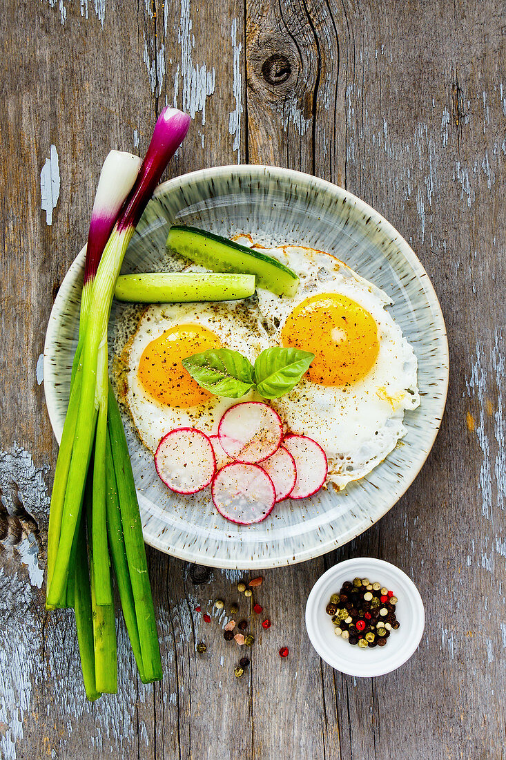 Homemade fried eggs in a plate, served with fresh vegetables