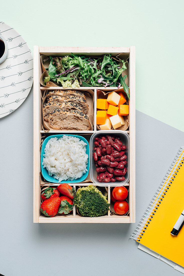 Food box with strawberry and tomatoes, broccoli and beans, rice and brad, cheese and arugula