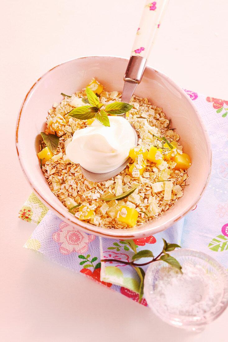 Amaranth and quinoa muesli with pineapple, mango, coconut flakes, mint and yoghurt