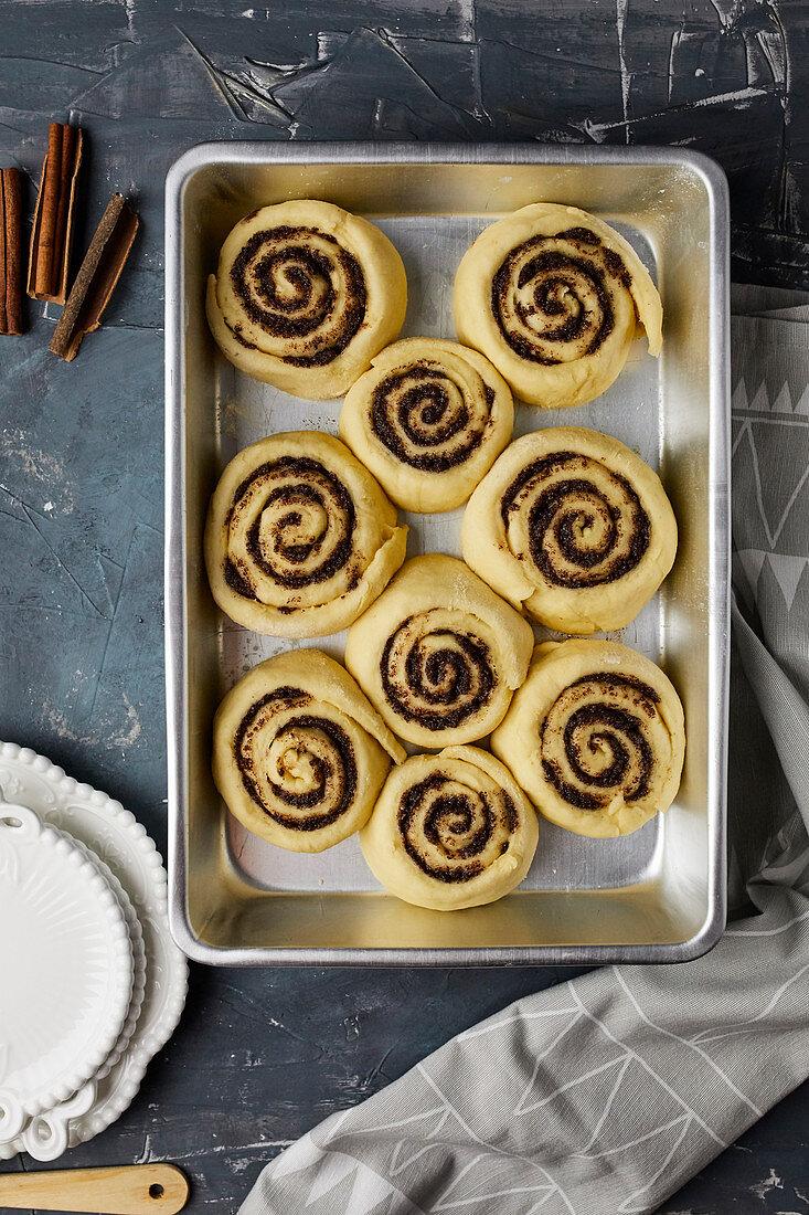 Raw cinammon rolls in baking tin