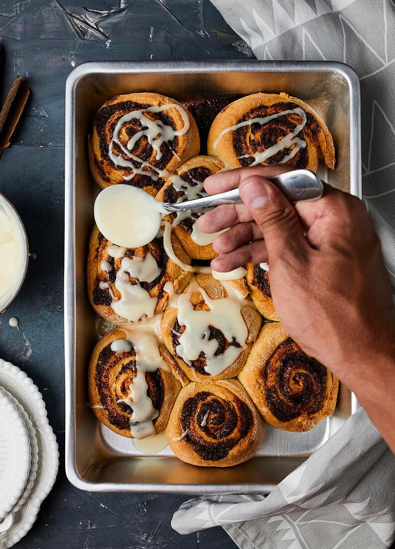 Drizzling sugar glaze over cinnamon rolls