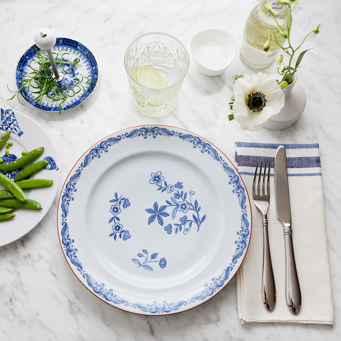 A place setting with floral plates, cutlery and a cloth napkin
