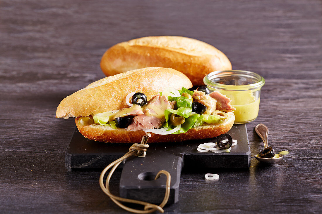Pan bagnat - savory tuna baguette from Provence with olive, mustard, lettuce, onion and vinegar