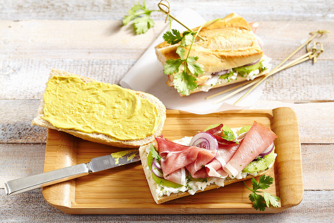 Baguette sandwich with kiwi, cottage cheese, smoked ham, coriander leaves and onion