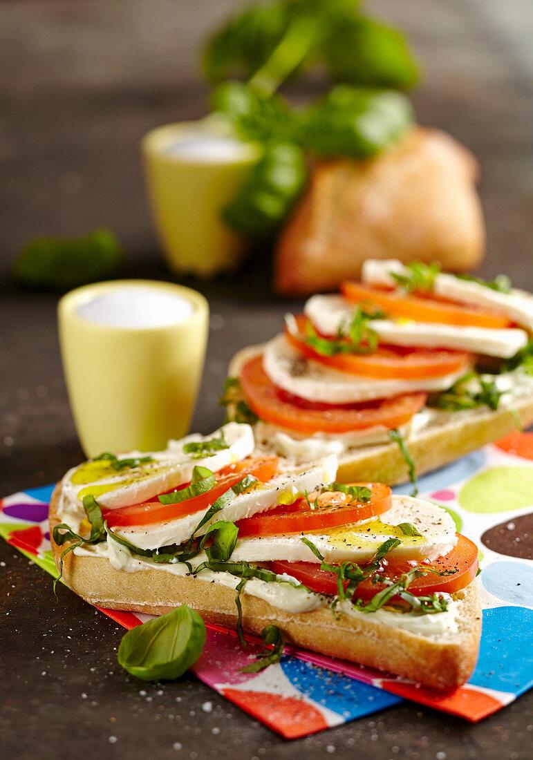 Caprese sandwich with tomato, mozzarella, basil and olive oil