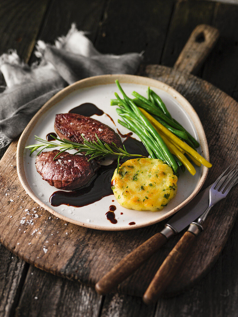 Ostrich medallions with a potato cake and beans