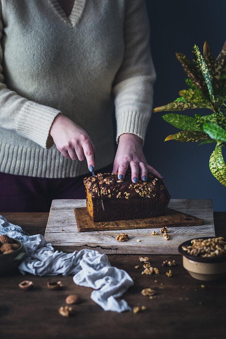 Woman slicing vegan pumpkin bread with walnuts