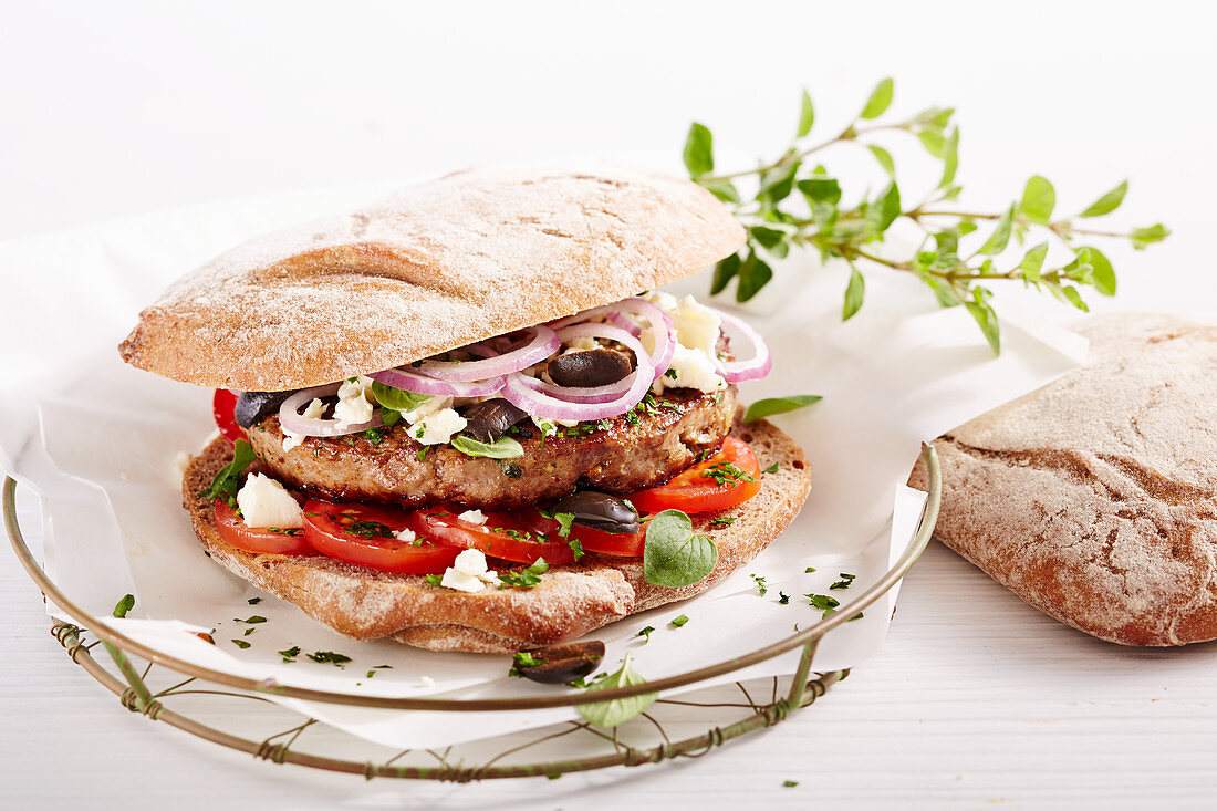 A lamb burger in South Tyrolean Vinschgau rolls with olives, feta, onion and tomato