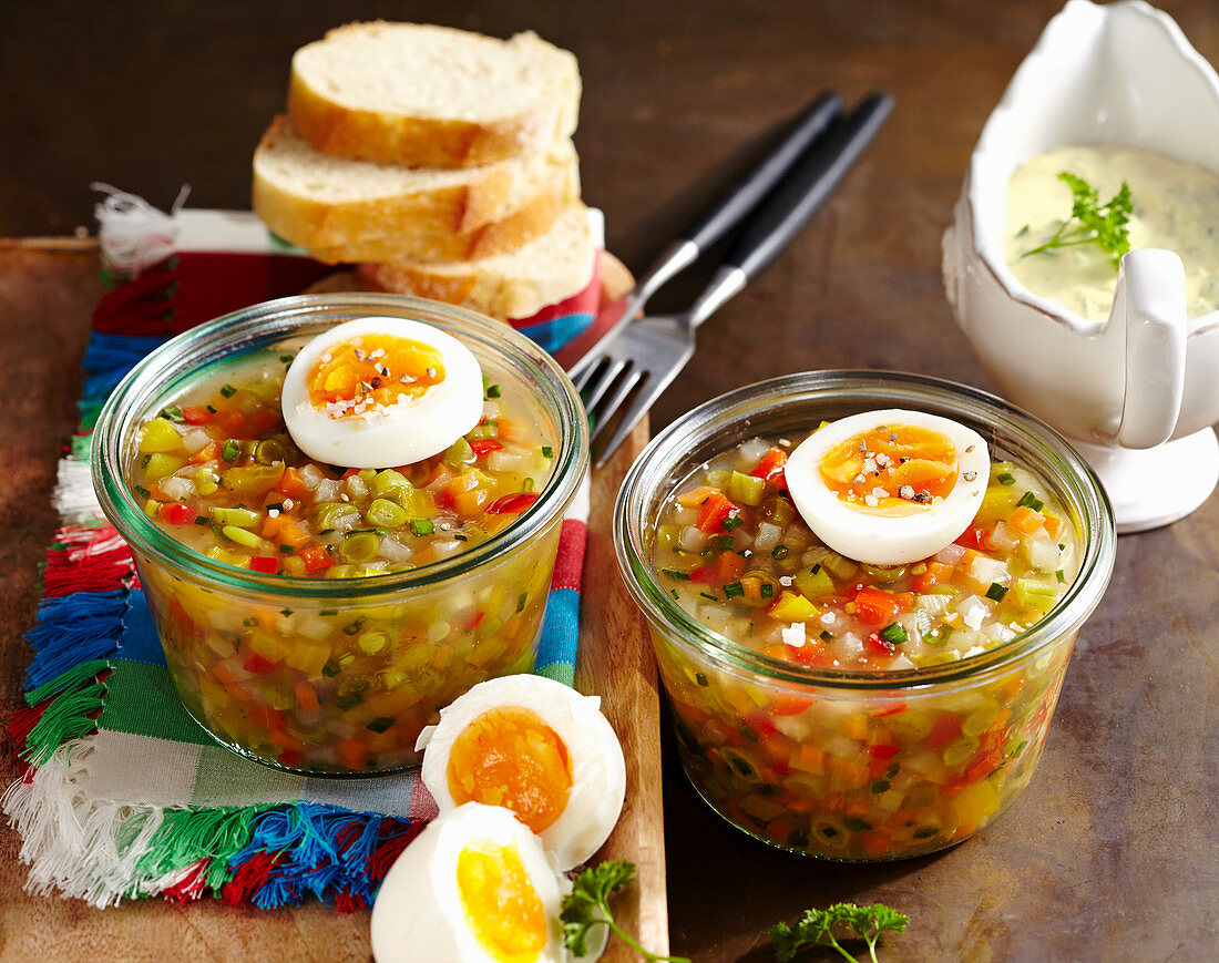 Vegetarian vegetable jelly with agar agar, boiled egg, baguette slices and chive sauce