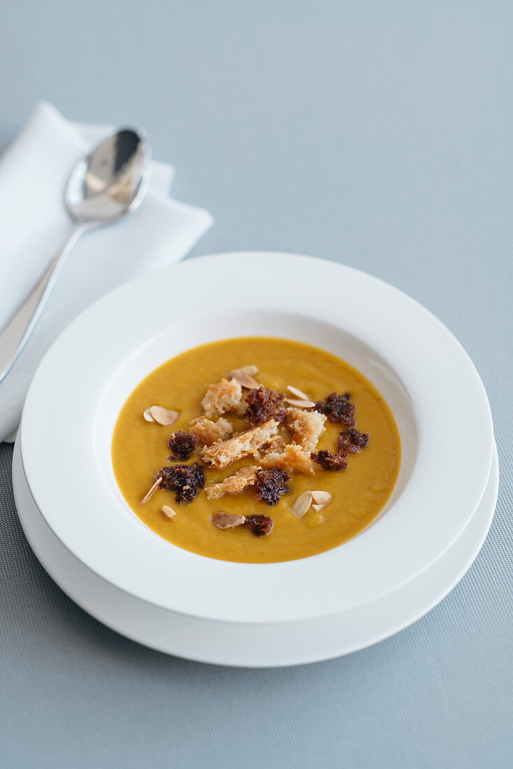 Cream of pumpkin soup with crispy fried sausage meat and almond crumbles