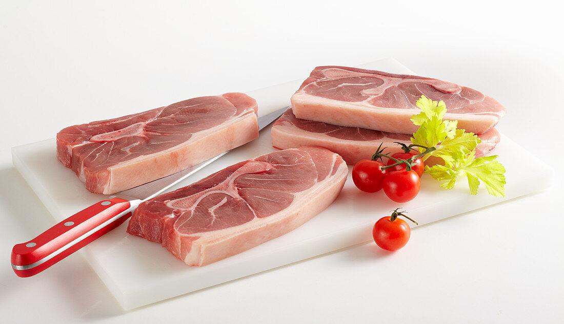 Raw pork shoulder in four slices (lumberjack steaks)