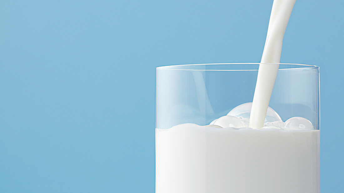 Milk pouring into glass with bubbles against light blue background