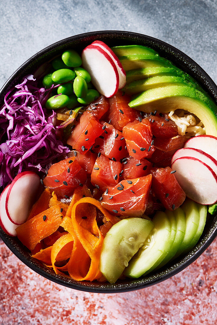 Poke bowl from overhead with gray stone surface on top and red mottled surface below