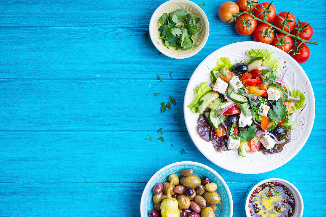 Bowl with fresh greek salad, tomatoes, olives, olive oil on wooden table