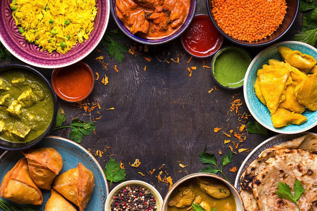 Assorted indian food on dark wooden background