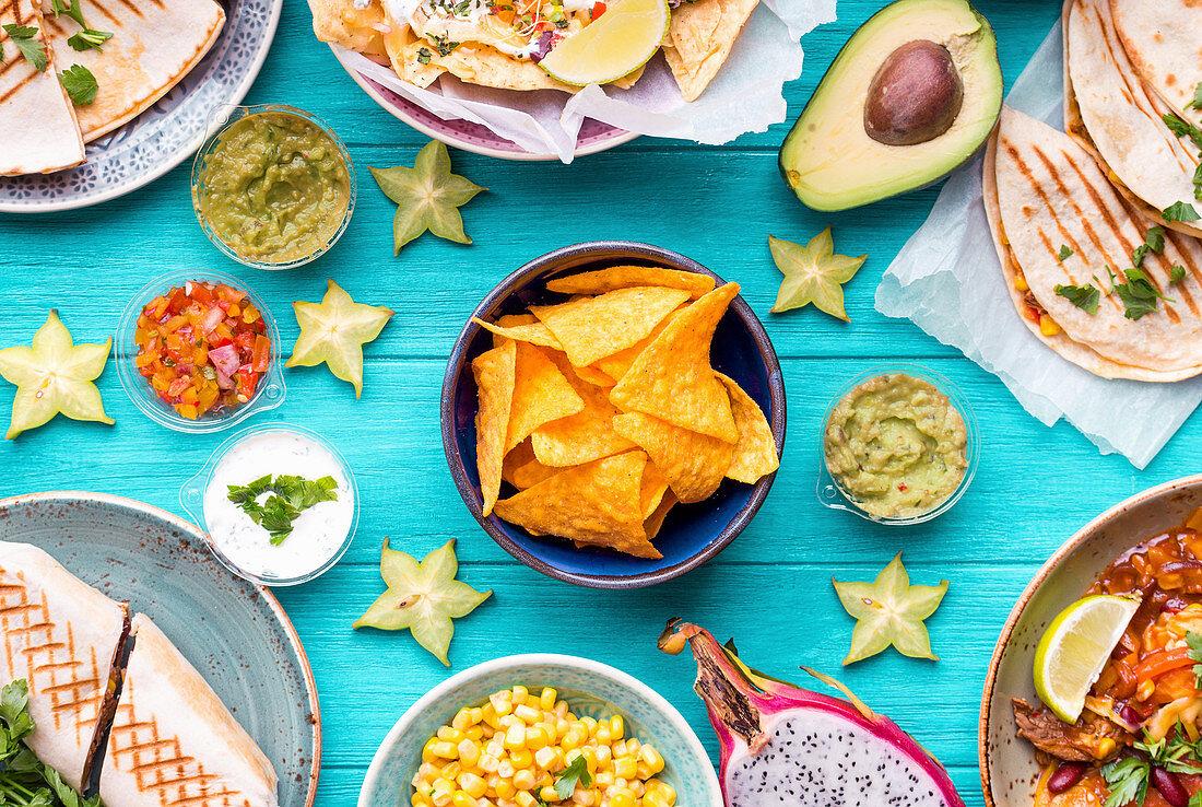 Assorted mix of traditional Mexican food (Cheese nachos, tacos, guacamole, quesadilla, burrito, fajitas, tortilla chips, Mexican fruits)