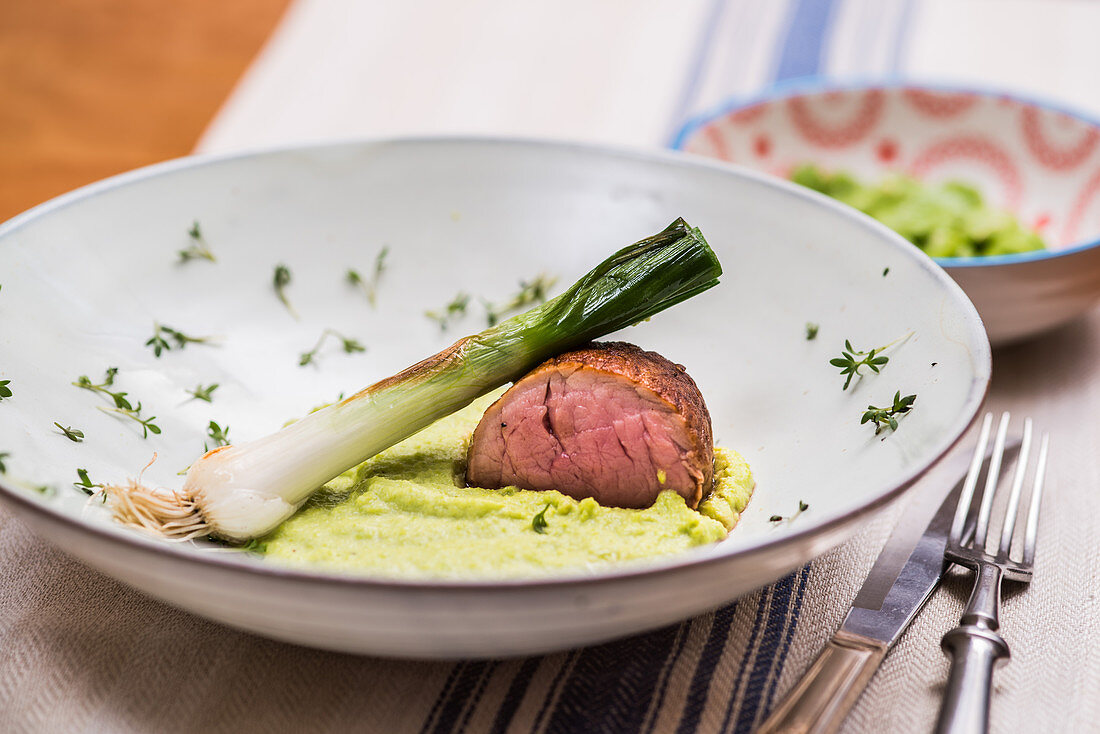 Low-cooked pork fillet with broad bean puree and braised green onion
