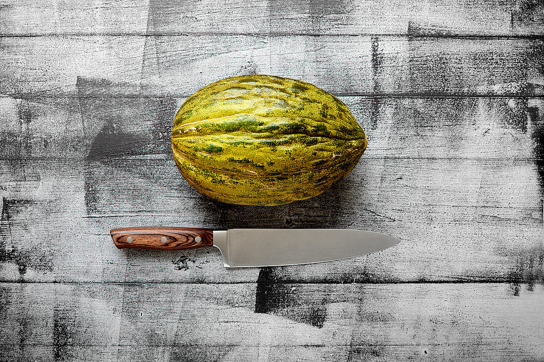 Santa Claus melon on a wooden background with a knife